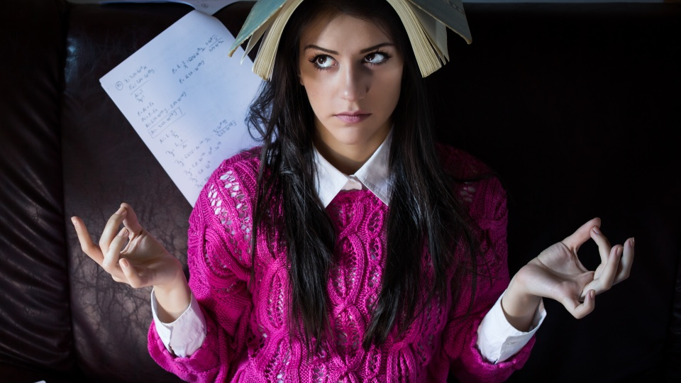 Funny looking brunette woman student trying to study in her room